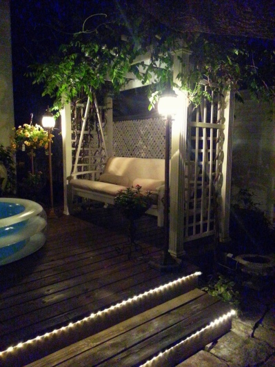the outdoor floor lamps on each side of the porch swing-